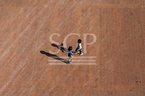 Montepulciano, Tuscany, Italy. Two children play in a piazza with red herringbone brick design paving.