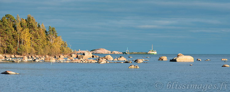 A ship threads its way through the rocky archipelago islands of southern Finland in autumn.