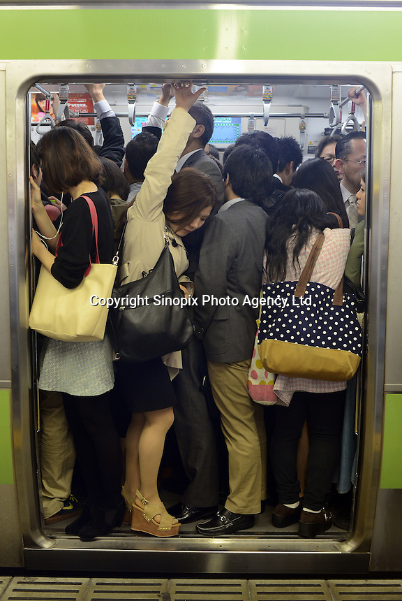 Passengers squeeze onto full trains during morning rush hour, Shinjuku, Tokyo. With up to 4 million passengers passing through it every day, Shinjuku station, Tokyo, Japan, is the busiest train station in the world. The station was used by an average of 3.64 million people per day.  That's 1.3 billion a year.  Or a fifth of humanity. Shinjuku has 36 platforms, and connects 12 different subway and railway lines.  Morning rush hour is pandemonium with all trains 200% full. <br /> <br /> Photo by Richard jones / sinopix