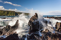 Waves crash onto lava rocks on the shore of Nua'ailua Bay at Keanae Lookout, on the way to Hana, Maui.