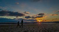 The sun sets over Swansea Bay, Wales, UK. Sunday 03 January 2021