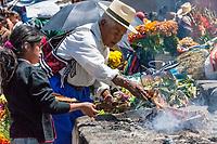 Chichicastenango, Guatemala.  Quiche (Kiche, K'iche') Man Adding Fuel to ceremonial Fire outside the Church of Santo Thomas, Sunday Morning.