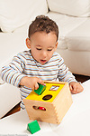 16 month old toddler boy playing with a shape sorter, trying to fit piece inside