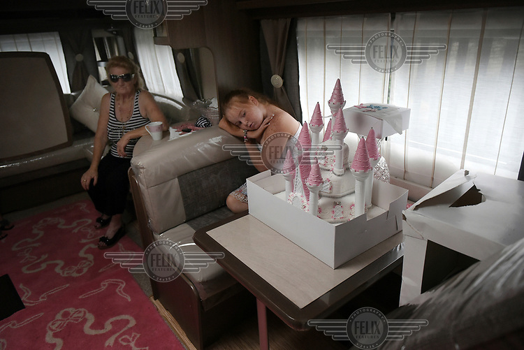 Irish Traveller Viviana Sheridan looks at her First Holy Communion celebration cake while her grandmother Jeany sits behind her in the family trailer which is parked on the roadside as they pass through Yorkshire.
