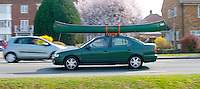 Car carrying a long, narrow canoe on its roof rack.