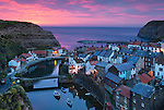 Great Britain, England, North Yorkshire, Staithes: Sunrise over fishing village.