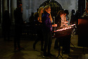 Lisbon, Portugal. 15.04.2016. People light canldes in memory of a loved one, in the cathedral, Alfama, Lisbon. Photograph © Jane Hobson.