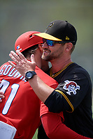 Pittsburgh Pirates coach Scott Mitchell hugs former Pirates coach Adam Godwin (41) during a minor league Spring Training game against the Philadelphia Phillies on March 13, 2019 at Pirate City in Bradenton, Florida.  (Mike Janes/Four Seam Images)