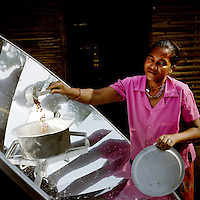 A woman with her new solar cooker at a Bhutanese refugee settlement. With the financial help of the Dutch Council for Refugees, a total of 6,300 solar cookers will be distributed amongst the Bhutanese refugees living in the region. The solar cookers consist of a reflective, aluminium, parabolic-shaped device that concentrates the sun's rays onto cooking pots placed on a frame in the centre of the dish. The dish has to be adjusted to the new position of the sun around every 10 minutes. It takes about 55 minutes to prepare a cooked meal on a sunny day and it is hoped that using the solar cookers will alleviate pressure on resources and reduce kerosene consumption by 75%...