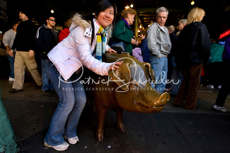Tourists take pictures with a bronze pig at Pike Place Market in Seattle Washington.