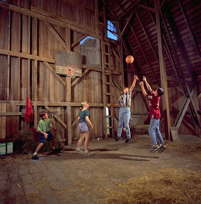 A group of farm children play basketball in a barn.