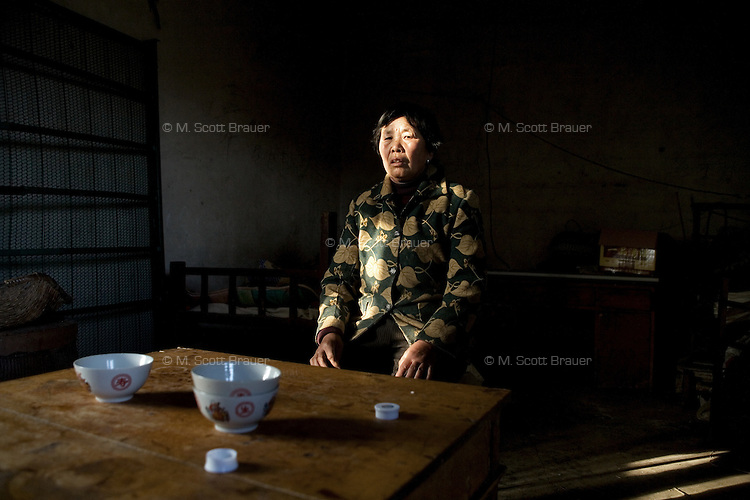 Guo Yu Hua sits in her home in Fanzhuang Village, Gangyun County, Jiangsu Province, China.  Guo Yu Hua is the aunt of Fan Jian Bo, 11, who was orphaned in 1998, who now lives with his aunt and uncle.  The boy's father died of cancer in 1998.  According to Amity Foundation records, The boy's mother could not cope with the loss of her husband and committed suicide by drinking pesticides.  The boy's uncle has a cerebral embolism.  The family grows cabbages and melons to earn money...At the time of the picture, China's Amity Foundation charity, was investigating the family's situation in preparation to raise money to financially support these children and other orphans in similar situations.  With Amity's support, each orphan, aged 6-12, would receive approximately 1,400 RMB annually (about 200 USD) to pay for the cost of living. Amity works to keep children out of the institutional orphanages in China, preferring to provide monetary assistance that can help maintain a family environment for the orphans it helps.