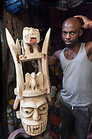 Nigeria. Enugu State. Enugu. Ogbete Main Market is the biggest commodity market. An Igbo handworker carves traditional wooden masks and sells them to customers. The large wooden sculpture is an Agaba mask which is a huge and heavy mask that stood for the power and aggressiveness of youth. The mask has always been closely associated with the identity, masculinity and quests for power and autonomy of young men. Ogbete main market is the choice market for wholesale buyers and sellers. Enugu is the capital of Enugu State, located in southeastern Nigeria. 2.07.19 © 2019 Didier Ruef