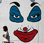 A local woman walk past a wall mural on N 5th Street, Williamsburg near Bedford street and the East River in Brooklyn, New York.
