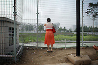 """CHINA. Beijing. A woman peers through a fence, trying to catch a glimpse of the new Olympic park. In recent years construction has boomed in Beijing as a result of the country's widespread economic growth and the awarding of the 2008 Summer Olympics to the city. For Beijing's residents however, it seems as their city is continually under construction with old neighborhoods regularly being razed and new apartments, office blocks and sports venues appearing in their place. A new Beijing has been promised to the people to act as a showcase to the world for the 'new' China. Beijing's residents have been waiting for this promised change for years and are still waiting, asking the question """"Where's the new Beijing?!"""". 2008."""