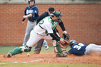 Charlotte 49ers catcher Charlotte 49ers assistant coach Brandon Hall (29) can't handle the throw as Dan Lawrence (38) of the Akron Zips scores the tying run in the top of the 9th inning at Hayes Stadium on February 22, 2015 in Charlotte, North Carolina.  The Zips defeated the 49ers 5-4.  (Brian Westerholt/Four Seam Images)