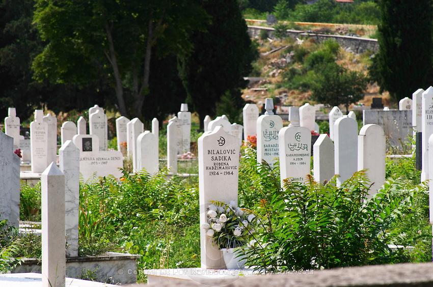 A grave yard church yard burial place with many recent graves with narrow and high white grave stones. Trebinje. Republika Srpska. Bosnia Herzegovina, Europe.