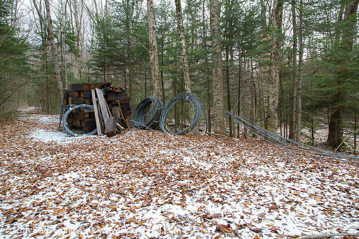 November 2012, Pemigewasset Wilderness - Remnants of a 180 foot suspension bridge that once crossed the East Branch of Pemigewasset River along the Wilderness Trail at the East Branch & Lincoln Railroad's Trestle 17 site in Lincoln, New Hampshire. The bridge was removed in 2009 because of public safety issues and these remains are slowly being removed from the wilderness area. Per the Wilderness Act, only non-motorized hand tools can be used to cut these support beams. This image was taken at the end of November 2012.