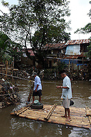 Local men stand on a river raft in a slum community in central Jakarta.<br />