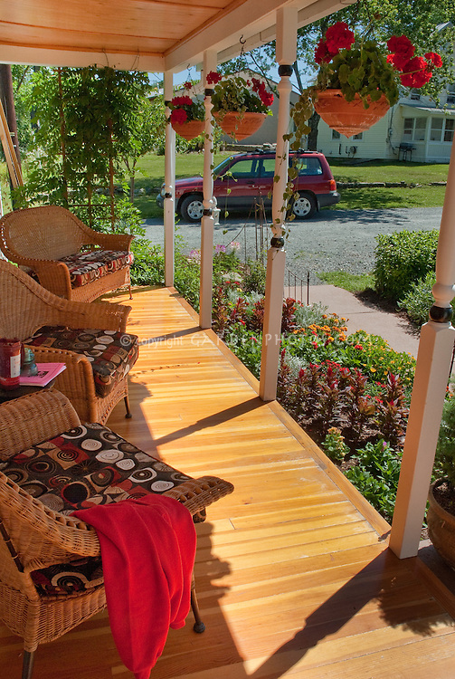 Front porch garden of house, entry landscaping, entrance, wicker chairs, wood flooring, columns, hanging baskets