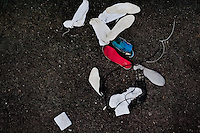 """White socks and insoles of alleged Mara gang members are seen thrown away after the initial search on the yard at the detention center in San Salvador, El Salvador, 20 February 2014. Although the country's two major gangs reached a truce in 2012, the police holding cells currently house more than 3000 inmates, five times more than the official built capacity. Partly because the ordinary Mara gang members did not break with their criminal activities (extortion, street-level distribution of drugs, etc.), partly because Salvadorean police still applies controversial anti-gang law which allows to detain almost anyone for """"suspicion of gang membership"""". Accused young men are held in police detention centers where up to 25 inmates may share a cell of five-by-five metres. Here, in the dark overcrowded cages, under harsh and life-threatening conditions, suspected gang members wait long months, sometimes years, for trial or for to be transported to a regular prison."""