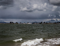 Dark clouds float over San Francisco Bay with the San Francisco skyline in the background.  Seen from Crown Beach in Alameda, California.