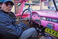 Cuba, Havana.  Taxi Driver Driving a 1957  Ford Convertible.
