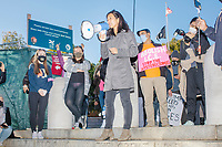 """Boston City councilor and mayoral candidate Michelle Wu uses a bullhorn to speak to a crowd gathered in Boston Common for the 2020 Women's March protest in opposition to the re-election of US president Donald Trump in Boston, Massachusetts, on Sat., Oct. 17, 2020.<br /> The sign here reads """"Abolish ICE / Stop the hysterectomies,"""" a reference to recent reporting that immigrant women held in ICE facilities were given hysterectomies without their consent."""