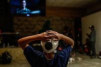 """Un joven observa la televisión durante la cena.  <br /> <br /> Migrantes reciben atención medica, alimentación, aseo personal y un lugar para descansar en el comedor Comunitario de la Colonia San Luis de Hermosillo Sonora.<br /> <br /> La Caravana del Migrante con un contingente de alrededor de 600 personas en su mayoría de origen centroamericano, arribo a Hermosillo Sonora a bordo del tren conocido como """"La Bestia"""", provienen de la frontera Sur del País y con rumbo a la ciudad de Mexicali donde continuaran el viaje hasta Tijuana.<br /> La caravana tiene como objetivo solicitar <br /> asilo a Estados Unidos y algunos integrantes piensan solicitar una visa humanitaria en México para laborar en los campos de Sonora y Baja California.<br /> Photo: NortePhoto/Luis Gutiérrez)"""