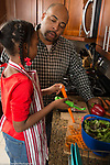 Father in kitchen with 8 year old daughter, talking, food preparation making salad