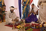 Hindu family from Sri Lanka living in Mitcham South West London celebrate their 16 years old daughter coming of age party. UK coconut milk symbolises health and prosperity, her brother cracks open a coconut. Brother who will pour coconut milk over her head.