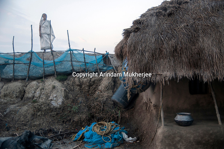 In village after village across this region, there are similar tales of mourning, young widows whose husbands have been killed by tiger. Here, a widow stands on the embankment at the back of her thatched house.