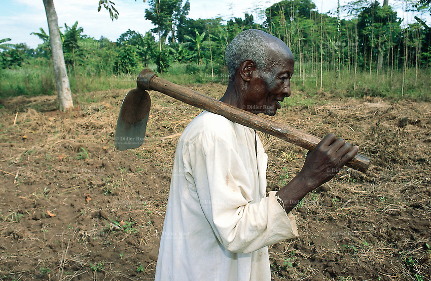 Uganda. Kayunga district. Nnongo. An old man carries on his shoulder a mattock used to work in the fields. The man wears a traditional cloth, a djelaba. © 2004 Didier Ruef