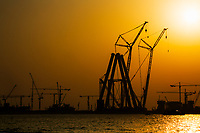 Colorful sunset on the construction and huge harbor crane silhouettes, above the Persian Gulf Sea, in Dubai, United Arab Emirates, Asia