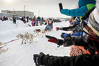 Ellen Halverson is greeted as she runs down Broadmoore street shortly after leaving the start line in Fairbanks on Monday March 9 during the 2015 Iditarod. <br /> <br /> (C) Jeff Schultz/SchultzPhoto.com - ALL RIGHTS RESERVED<br />  DUPLICATION  PROHIBITED  WITHOUT  PERMISSION