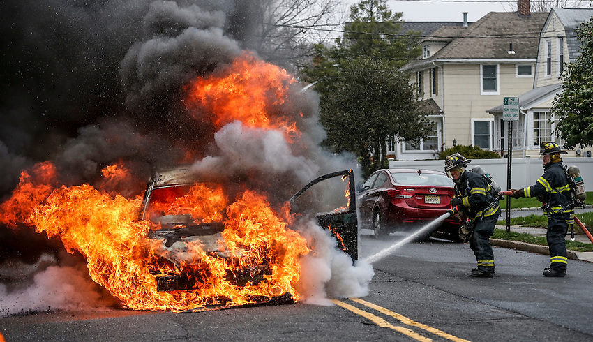 MANASQUAN, NJ — April 1, 2016 —Manasquan firefighters Kevin McCredie and Tom Schofield get water on a 2000 Ford Focus that is fully engulfed in flames at about 9:40am on Broad Street, here. The driver of the vehicle, Nancy Trapani, was not injured.  photo by Andrew Mills