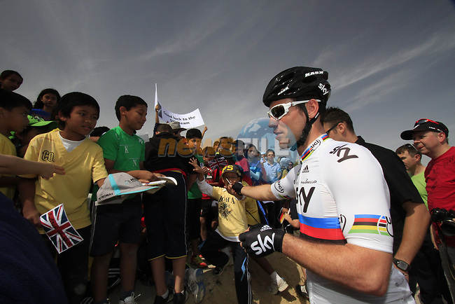 Sky Procycling rider World Champion Mark Cavendish (GBR) signs autographs for local school children before the start of the 3rd Stage of the 2012 Tour of Qatar running 146.5km from Dukhan Souq, Dukhan to Al Gharafa, Qatar. 7th February 2012.<br /> (Photo Eoin Clarke/Newsfile)