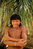 Roraima, Brazil. Laughing Yanomami man under a palm tree.