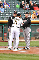 Keith Johnson (21) of the Salt Lake Bees meets with Steve Scarsone (23) and Greg Sparks (17) of the Sacramento River Cats prior to the game at Smith's Ballpark on April 3, 2014 in Salt Lake City, Utah.  (Stephen Smith/Four Seam Images)