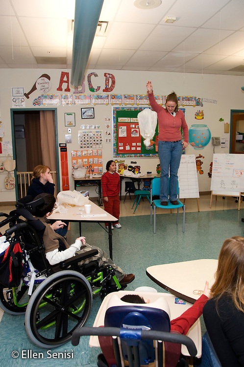MR / Albany, NY.Langan School at Center for Disability Services .Ungraded private school which serves individuals with multiple disabilities .Teacher prepares to drop egg as part of language arts lesson and science experiment while students watch. Lesson objectives are for students to predict whether a wrapped egg will break when dropped, as well as their use grasping and coordination skills. Students have mixed disabilities including cerebral palsy and muscular dystrophy.(other images from this sequence available).MR: AH-cfds.© Ellen B. Senisi