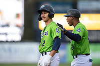 Kane County Cougars center fielder Alek Thomas (2) is congratulated by Carlos Mesa (24) after reaching first base during a Midwest League game against the Cedar Rapids Kernels at Northwestern Medicine Field on April 28, 2019 in Geneva, Illinois. Cedar Rapids defeated Kane County 3-2 in game two of a doubleheader. (Zachary Lucy/Four Seam Images)