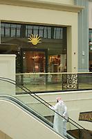 United Arab Emirates, Dubai, Emirati men on escalator, shopping mall