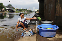 A woman washed clothes in a canal in central Jakarta. The city's drainage was built by the dutch during colonial times however many of them have fallen into disrepair and are clogged with refuse.