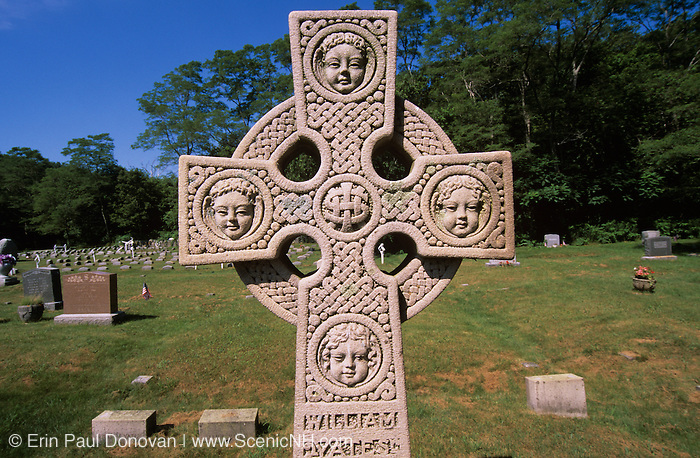 Cross headstone with faces on it at Beechbrook Cemetery in Gloucester, Massachusetts USA.