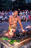 "A Hawaiian man dressed in a traditional  garment, makes a """"shaka"""" sign while standing over a roasted kalua pig at the Kona Village Resort. Seated tourists watch the ceremony."