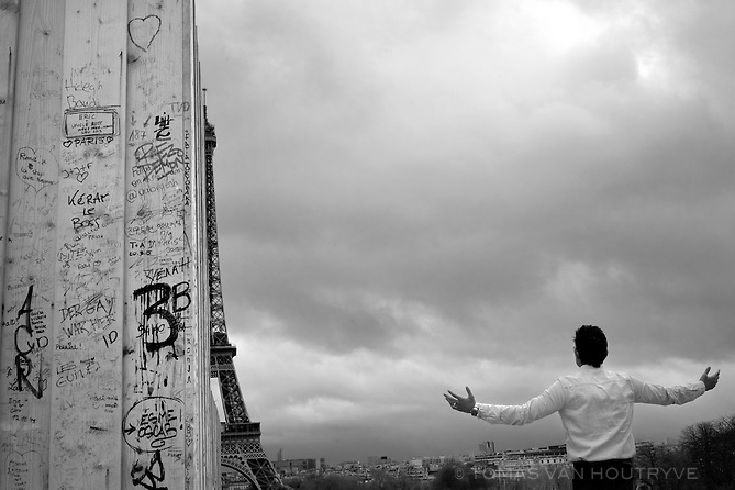 A tourist reacts to the site of the Eiffel Tower, partially hidden by a temporary wall around a construction site at Trocadero in Paris, France, four days after coordinated terrorist attacks struck the heart of the French capital. Seen in the background, the Eiffel Tower was closed to visitors again after briefly opening Monday.