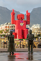 """South Africa, Cape Town.  Nobel Square Statues of Desmond Tutu and FW de Klerk. Sculptor Claudette Schreuders.  In background is the """"Lego Man"""" sculpture made of 4200 plastic  Coca Cola crates.  Designed by Porky Hefer."""