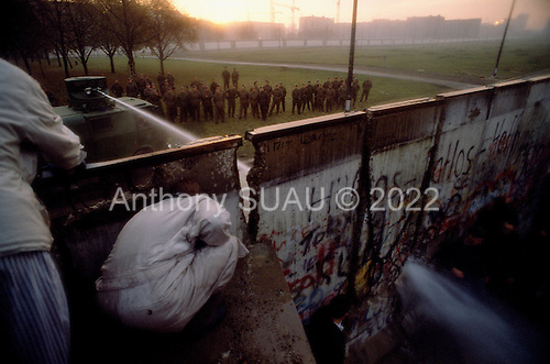 Berlin, Germany<br /> November 11, 1989<br /> <br /> East German police use a water canon to try and stop a group of West Germans as they break through the wall at the Brandenburg Gate. The East German government lifts travel and emigration restrictions to the West on November 9, 1989.