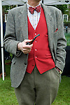 Man smoking pipe wearing red waistcoat and tweed sports jacket coat.