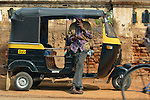 India, Karnataka, Mysore. Autorikshaw driver smoking while having a break.